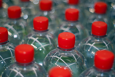 background - plastic bottles with drinking water with red stoppers Stock Photo