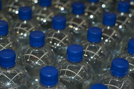 background - plastic bottles with drinking water with blue stoppers