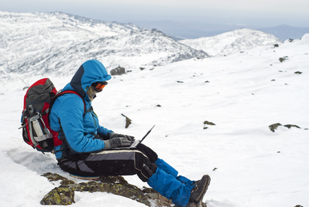 traveler working with a laptop in winter on top of a mountain during the snowfall