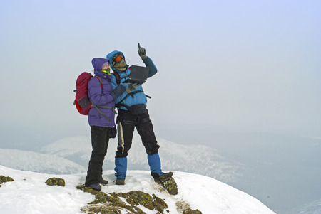 two hikers on a winter mountain peak with a laptop Stock Photo