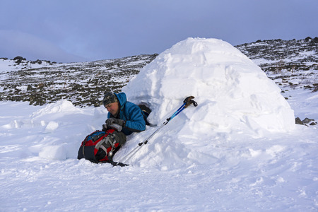 hiker pours himself a tea from a thermos, sitting in a snowy hut igloo against a background of a winter mountain landscape