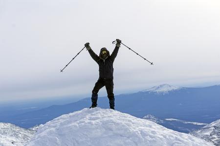 climber triumphs, reaching the top of the mountain Фото со стока