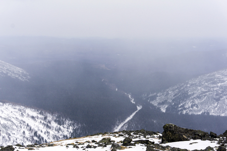 deep wooded gorge in the mountains of the Northern Urals during a heavy snowfall, view from the cliff Stock Photo