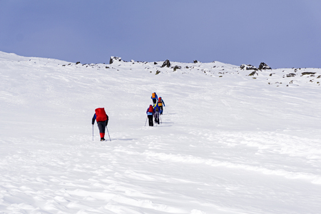 group of hikers on snow-covered mountain slope under a bright blue sky