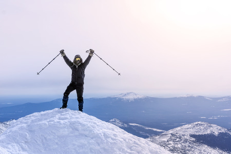 climber exults reaching the top of the mountain peak Фото со стока