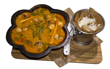 hot Thai soup tom yum (or tom yam) in a curly wooden plate and a bucket of rice served on a board isolated on a white background Stock Photo