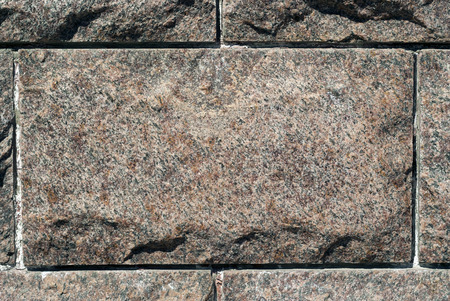 rough granite rectangular block in the composition of masonry wall