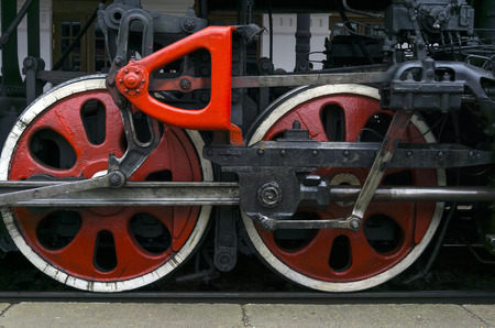 fragment of vintage functioning steam locomotive standing at station, closeup, visible driving wheels with a system of pistons, connecting rods and levers