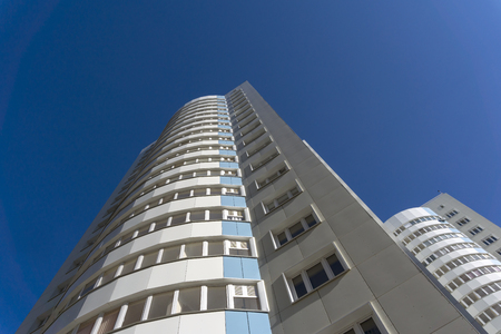 Multi-storey residential buildings go skyward in perspective ona background of blue sky   Stock Photo