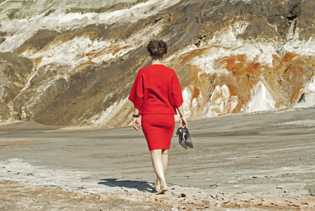 woman in a business red dress, taking off her shoes, walking barefoot into a deserted canyon with her back to the viewer   Stok Fotoğraf