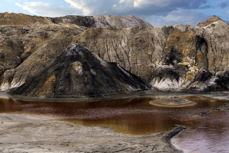 lake with red water with dissolved pyrite salts in the desert landscape of a spent quarry Banco de Imagens