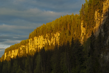 Rocky cliffs in the northern forest, lit by the rays of midnight sun 写真素材
