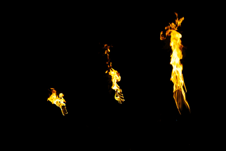 Three flames of a torches in the dark on a black background, only the fires is visible