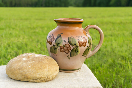 still life with a ceramic jug and loaf of rustic bread on a tablecloth against the background of a green meadow