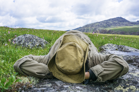 tired traveler in the mountains - a man in a hat and camp clothes resting lying on his back on a mountain plateau