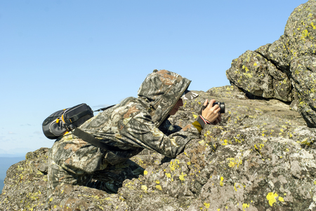 girl wildlife photographer in camouflage suit in the mountains hiding behind a stone photographing something Stock Photo