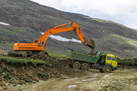 laying a road in a mountainous area, an excavator and a dumper during construction work