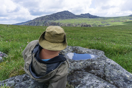 tired traveler in the mountains - a man in a hat and camp clothes resting, staring into the distance, lying on a mountain plateau