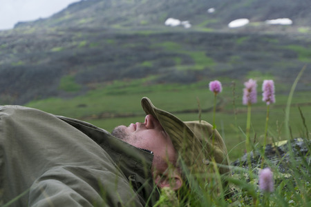 tired traveler in the mountains - a man in a hat and travel clothes resting, lying on his back in the alpine meadow on a mountain plateau
