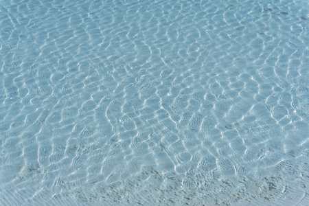 background, texture - blue water of a salt lake or tropical sea lagoon with a solar ripple over a white bottom