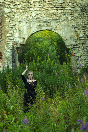 witch - young woman in black dress with ominous make-up conducts an sinister pagan rite among ancient ruins