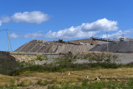 dumps of mined rock with spreader and working bulldozer, general view