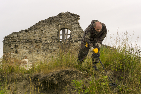 man with a metal detector scans the earth against a background of ancient ruins