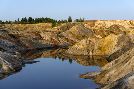 landscape - a fragment of a quarry of kaolin mining with beautiful multicolored slopes and a lake in the foreground Фото со стока