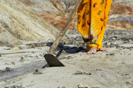 woman in a sari with a hoe in her hands in an arid, lifeless desert area 版權商用圖片