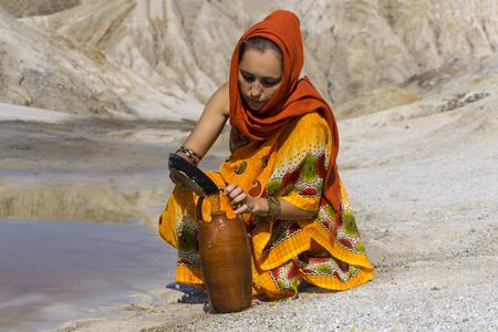 ragazza di aspetto orientale in sari e hijab riempie la brocca con l'acqua proveniente da una sorgente sporca nella zona arida
