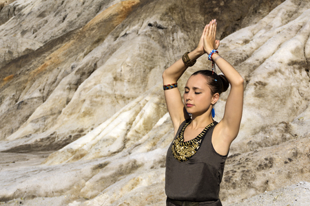 young beautiful woman stands with arms raised over her head, in a namaste position, outdoor against a background of desert rocks