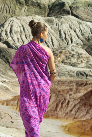 girl in a pink sari is standing with her back to the viewer outdoors against a backdrop of a desert landscape