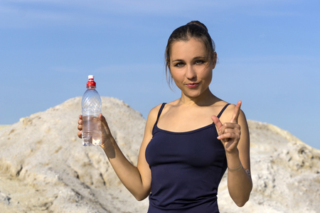 young slender athletic girl after playing sports outdoors holds a plastic water bottle and gestures to emphasize the importance of drinking water 版權商用圖片