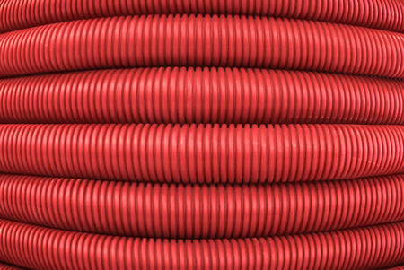 background - red corrugated flexible polymer tubes close up