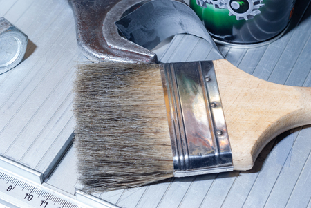 crafting table fragment with tools and brush to remove dust, closeup