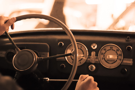 driving a vintage car; only the driver's hand on the steering wheel are visible, the dashboard is blurred; stylized as an old sepia photo with dust and noise