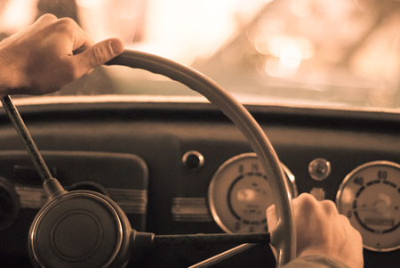 driving a vintage car; only the driver's hand on the steering wheel are visible, the dashboard is blurred; stylized as an old sepia photo with dust and noise Standard-Bild