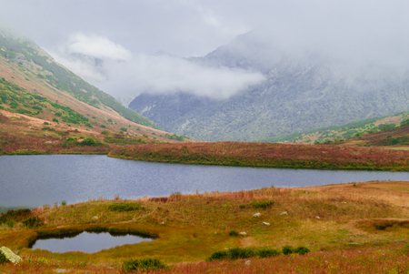 misty mountain valley with lush autumn vegetation and two small lakes, sheltered by low clouds