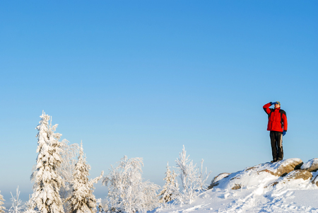 hiker man in winter sportswear looking into the distance standing on a cliff against the blue sky over a winter snow forest 版權商用圖片