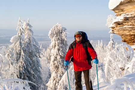 Traveler in windproof goggles and with poles for nordic walking standing in a frosty winter landscape near a beautiful cliff and looks into the frame