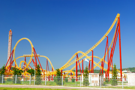 bright red and yellow roller coaster structures in the city's amusement park Stock Photo