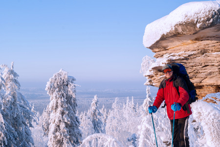 laughing traveler with backpack and poles for nordic walking standing in a frosty winter landscape near a beautiful cliff and looks into the frame