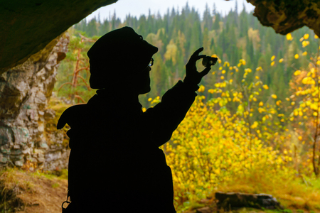 silhouette of a geologist examining a mineral sample found in a cave, on the background of an entrance with a brightly lit autumn forest 免版税图像