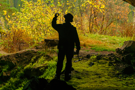 silhouette of a geologist examining a mineral sample found in a cave, on the background of an entrance with a brightly lit autumn forest Banco de Imagens