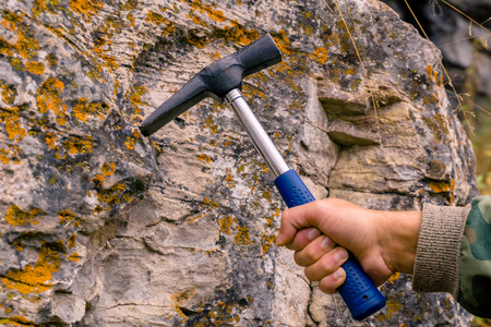 geologist's hand strikes a limestone mossy rock with a geological hammer to take a sample Stock Photo