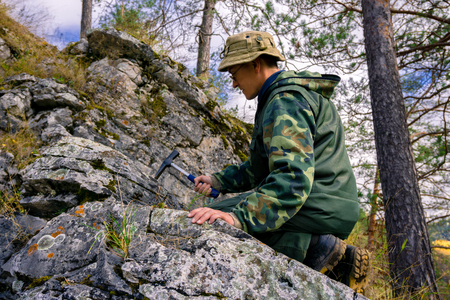 geologist using a geological hammer takes a rock sample outdoor Foto de archivo