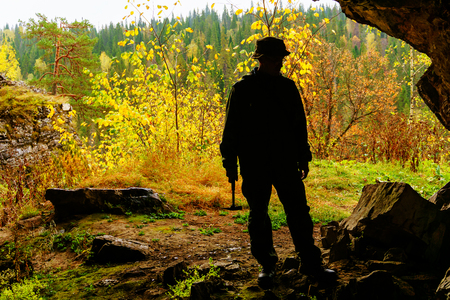 researcher with a geological hammer in his hands inspects a stone scree at the entrance to the cave against the backdrop of the autumn mountain landscape outside Stock Photo