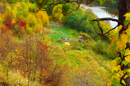 tourist camp with a tent and a bonfire in the autumn glade near the river bank, top view