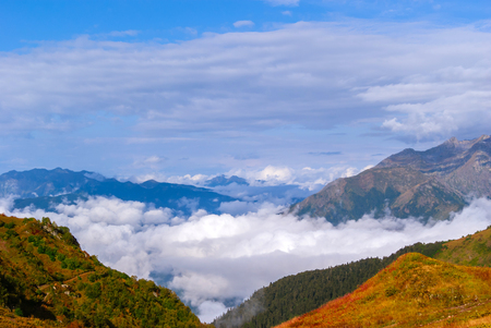 landscape - view from the mountain top on a sunny day to the valley hidden by low clouds Stock Photo