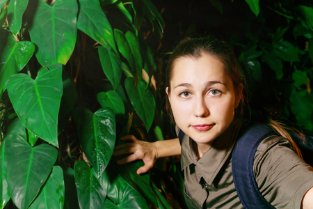 girl traveler in the jungle comes out of thicket of tropical plants into the sunlight Banco de Imagens